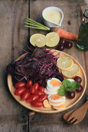 grapes and mushrooms: fresh red spinach salad and cream on wooden table