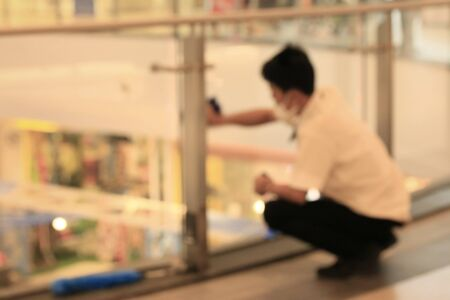 departmentstore: Blurred people wipe the glass in shopping mall