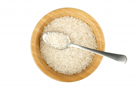 not full: wood bowl and spoon with raw rice isolated on white Stock Photo