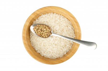 not full: wood bowl with raw rice and spoon with raw lentil isolated on white