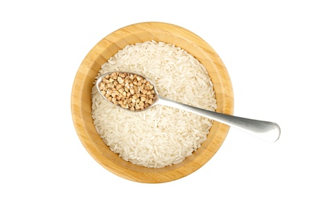 not full: wood bowl with raw rice and spoon with raw buckwheat isolated on white Stock Photo