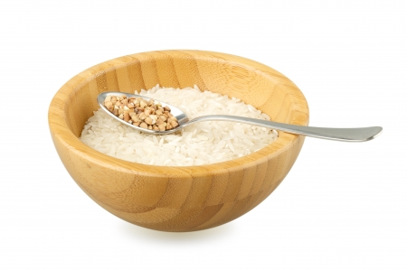 not full: bamboo bowl with raw rice and spoon with raw buckwheat isolated on white