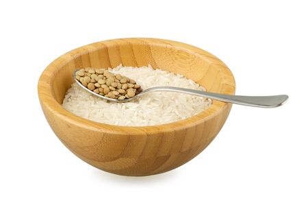 not full: bamboo bowl with raw rice and spoon with raw lentil isolated on white