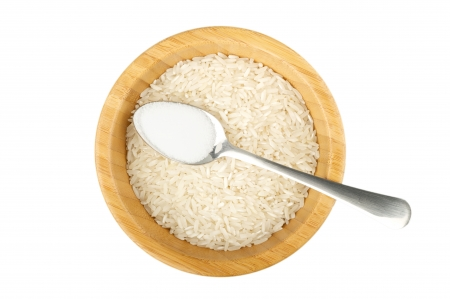 not full: wood bowl with raw rice and spoon with salt isolated on white
