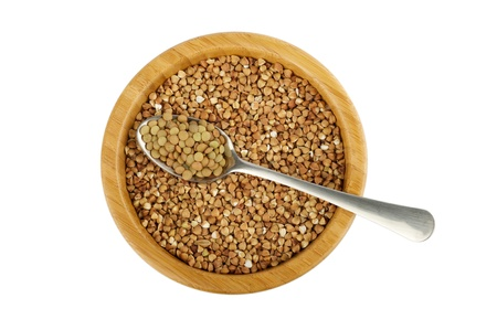 not full: wood bowl with raw buckwheat and spoon with lentil isolated on white