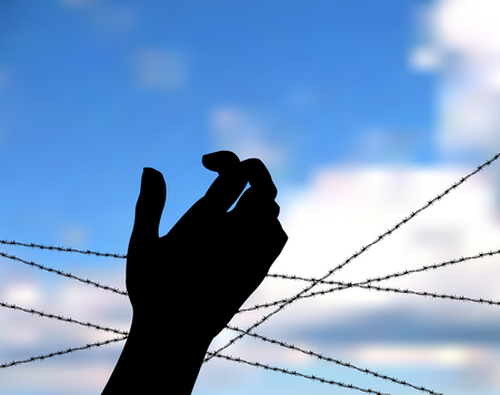 Hand Silhouette outstretched in supplication for help and Barbed wire against the blue sky. Concept of the refugees. Hand of a refugee or a prisoner against barbed wire and blue sky as background