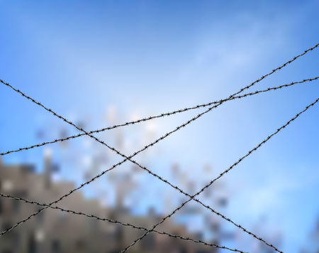 Barbed wire against blue sky. Protection or security concept. Sky bounded by barbed wire. The lack of freedom behind barbed wire. Metallic fence for barrier or property protection against sky Ilustrace