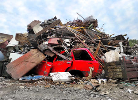 Retro red vehicle at junk yard. Broken steel garbage, vintage automotive parts and iron in heap waste for Recycling. Metal industry of rusted scrap - salvage business. Recycling Scrap pile disposal