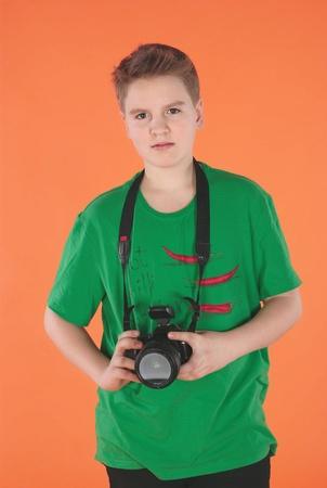 Young boy with photocamera. Orange background Stock Photo