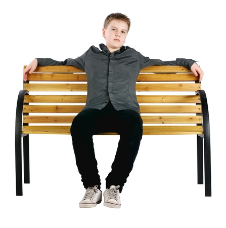 Relaxed boy sitting on bench Stock Photo