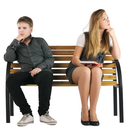 Boy and girl sitting on a bench and not looking at each other Stock Photo - 9271028