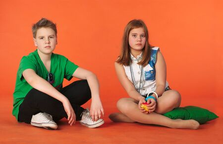 Boy and girl sitting on the floor. Orange background Stock Photo
