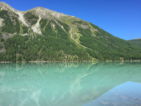 Beautiful turquoise Kucherla lake. Reflection of mountains in the water. Summer vacation in the mountains. Arrow image formed by reflection in the water. Russia, Altai Mountains. Imagens