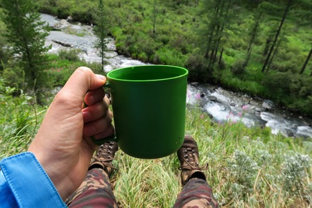 Tourist hand holding plastic mug. Camping image. Enjoying rest and mountain river and forest. Nomad life