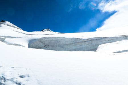 Mountain climbers walking on the glacier near the crack. View to the Berelskoe sedlo glacier. Belukha Mountain area. Altai Stok Fotoğraf