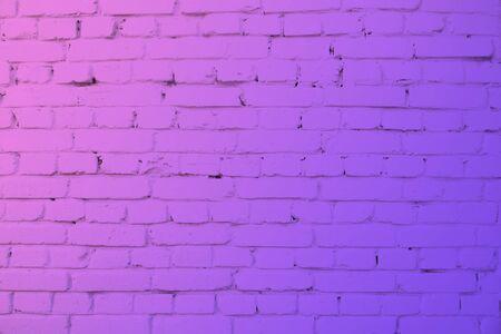 Pared de ladrillo con iluminación de neón. Colores modernos fondo morado y rosa.