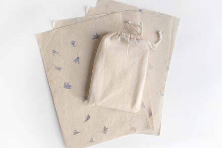 Mock up of tarot deck cotton bag with texture paper sheets on white background. Boho design of tarot cards pouch on white table with copy space for image or text.