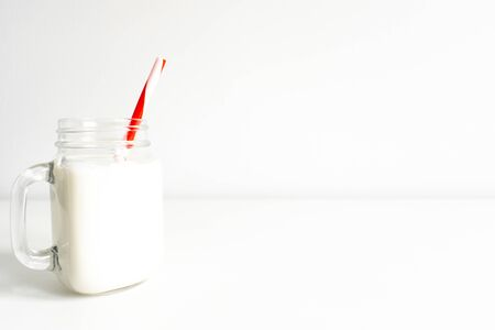 Old fashion milk jar. Mason jar with red striped straw on white background. Christmas milk