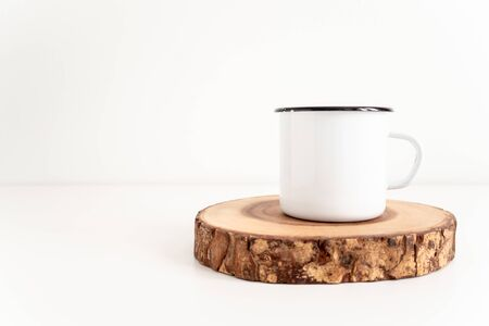 Enamel mug mock up with wooden cut tree section on a white table. Boho design of tin cup on white background with copy space for image or text