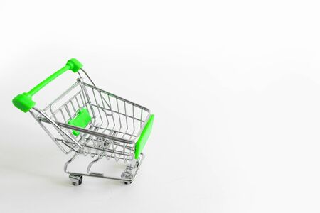 Shopping cart on white background. Small miniature shop trolley with space for your text. Copyspace mockup banner 写真素材