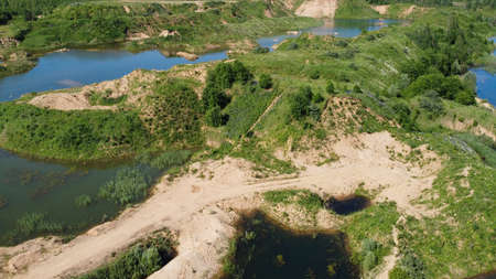Flooded and overgrown sand quarry. Lush green summer landscape for outdoors vacation, hiking, camping or tourism. Volokolamsk district, Moscow region. Sychevo beach, Russia