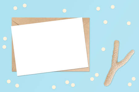 Mockup of horizontal postcard on a craft brown envelope with white porous coral. Boho rustic decorations flat lay. Summer beach theme. Mockup with copy space for your image or text