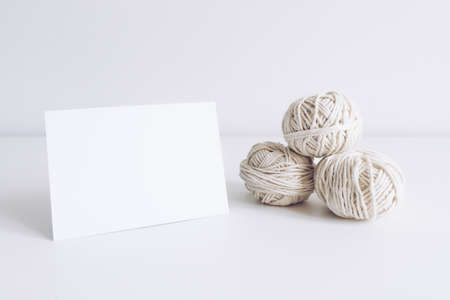 Horizontal postcard mockup with white yarn on a white table background. Threads of cord boho image. Space for text. For macrame and bohemian handicrafts banners and advertisement. Copyspace mock up