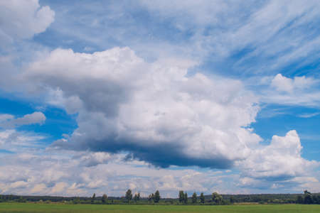 Picturesque summer landscape with white fluffy summer clouds on blue marvelous sky view background. Green meadow stock photography.