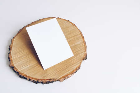 Mockup of vertical postcard on wooden cut tree section on white table. Boho design of postcard on white table with copy space for your image or text