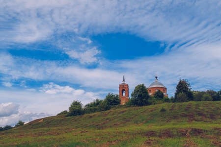 Old Christian orthodox church on the hill in sunny summer day with blue sky and clouds background landscape. Russia