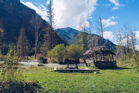 Camping place with old log house by the river flowing in the forest among trees and green lush bushes. Kucherla river in Belukha national park, Altai Mountains, Russia