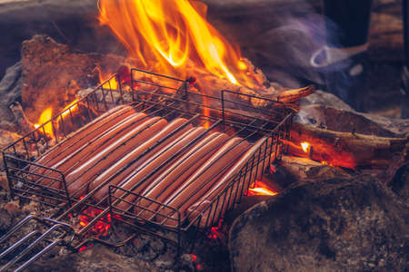 Sausages are grilled on fire. Camping in the countryside. Outdoors lifestyle barbecue cooking delicious meal