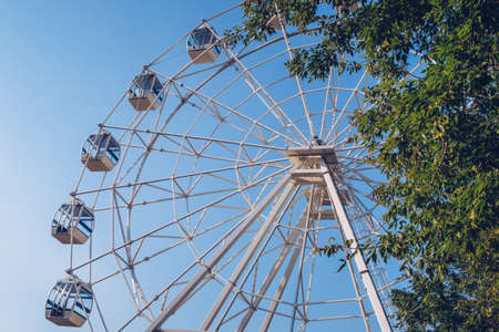 Ferris wheel on the background of the blue sky. Amusement park, fair, no people. Stock photography.