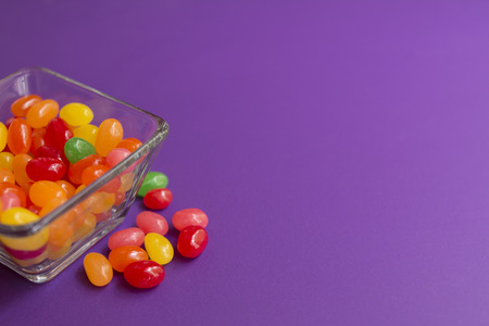 Colorful candies in candy on purple background