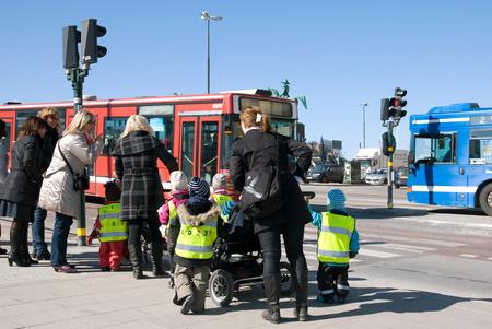 STOCKHOLM, SWEDEN - APRIL 14, 2010:Educators with kindergarten children dressed in reflective safety vests on crosswalk in the centre of Stockholm. Sweden