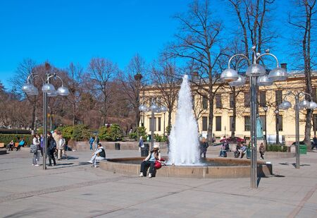 university fountain: OSLO, NORWAY - APRIL 12, 2010: People near fountain on the Johanne Dybwad Square. On the background is Johanne Dybwad monument and fragment of University of Oslo building