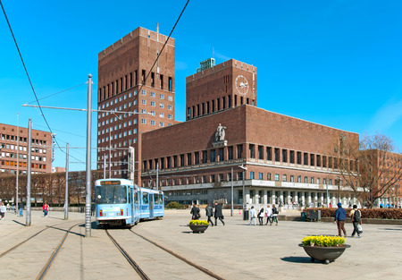 OSLO, NORWAY - APRIL 12, 2010: People and blue tram near the City Hall