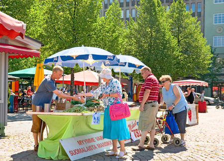 LAHTI, FINLAND - JULY 17, 2010: People buy fresh vegetables and berries on the Market Square in the center of Lahti