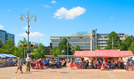 LAHTI, FINLAND - JULY 17, 2010: People rest and eat in cafes on Market Square in the center of Lahti. On the background is Alex Park Hotel