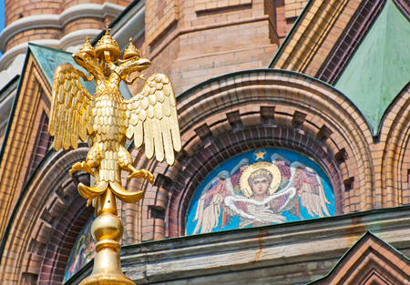 doubleheaded: SAINT - PETERSBURG, RUSSIA - JULY 15, 2014: Double-Headed Eagle in Golden Caps. n the background is the Bible winged angelic being. The Church of the Resurrection Savior on the Spilled Blood
