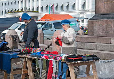 HELSINKI, FINLAND - APRIL 23, 2016: Finnish woman knits and sells colorful woolen goods on The Market Square (Kauppatori) near Gulf of Finland.