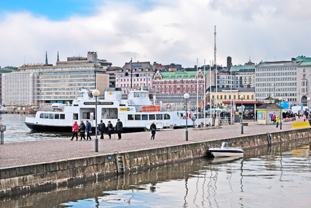 HELSINKI, FINLAND - APRIL 23, 2016: People walk on the quay near The Market Square and pier with ferry to Suomenlinna (Sveaborg) Fortress.