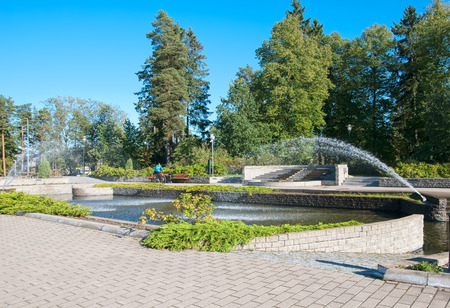 central european: IMATRA, FINLAND - SEPTEMBER 13, 2016: Woman on the bicycle near pool with fountains not far from Spa Hotel Rantasipi Imatran Valtionhotelli in the center of the town Editorial