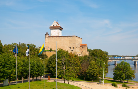ida: NARVA, ESTONIA - AUGUST 21, 2016: Hermann Castle (Hermannsfeste) on the bank of The Narva (Narova) River. On the right side is The Bridge of Friendship between Estonia and Russian Federation Editorial