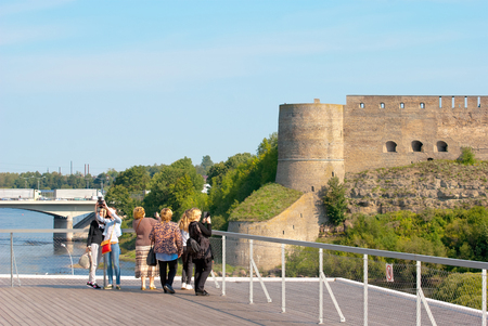 ida: NARVA, ESTONIA - AUGUST 21, 2016: People on observation deck in Estonian Town Narva take pictures in front of the Bridge of Friendship and Ivangorod Fortress on Russian territory