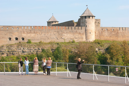 ida: NARVA, ESTONIA - AUGUST 21, 2016: People on observation deck in Estonian Town Narva take pictures in front of the fortress Ivangorod on Russian territory Editorial