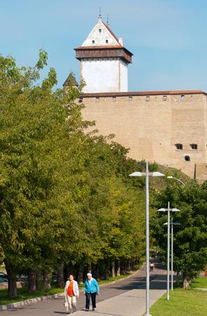 ida: NARVA, ESTONIA - AUGUST 21, 2016: People on Linnuse Street. On the background is Hermann Castle (Hermannsfeste) - medieval fortress.