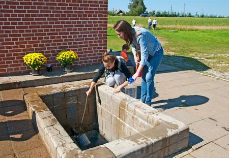 ida: KUREMAE, IDA-VIRUMAA COUNTY, ESTONIA - AUGUST 21, 2016: Young women take water from The Holy Spring on the place of Marian apparition. Located not far from Puhtitsa Orthodox Dormition Convent