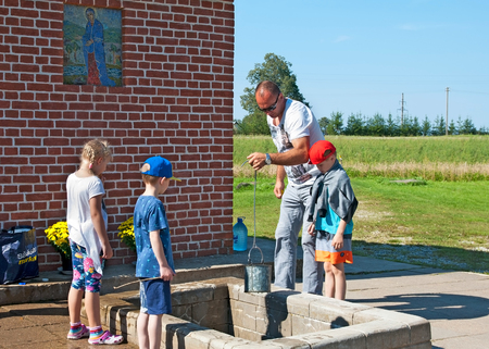 ida: KUREMAE, IDA-VIRUMAA COUNTY, ESTONIA - AUGUST 21, 2016: Man with children take water from The Holy Spring on the place of Marian apparition. Located not far from Puhtitsa Orthodox Dormition Convent Editorial