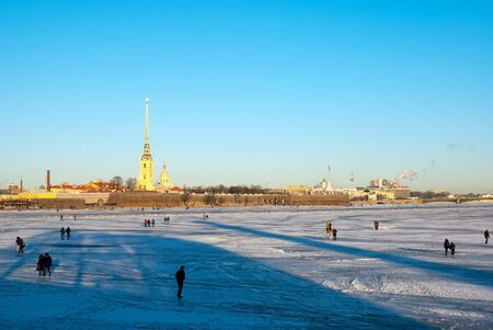 saints peter and paul: SAINT-PETERSBURG, RUSSIA, JANUARY 21, 2017: People walk on the Neva River ice near The Old Saint Petersburg Stock Exchange and Rostral Columns. On the background is Saints Peter and Paul Fortress